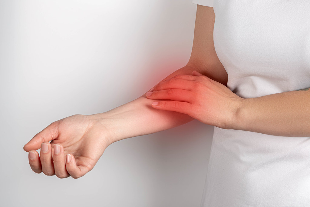 Pain in the arm, a woman touches a sore arm