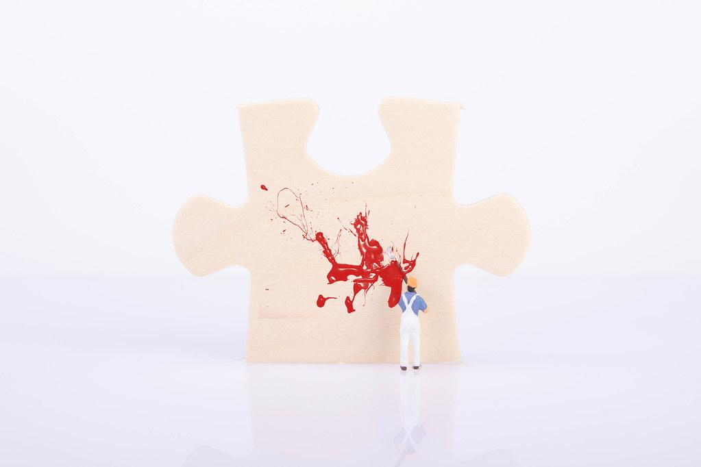 Painter painting a puzzle piece