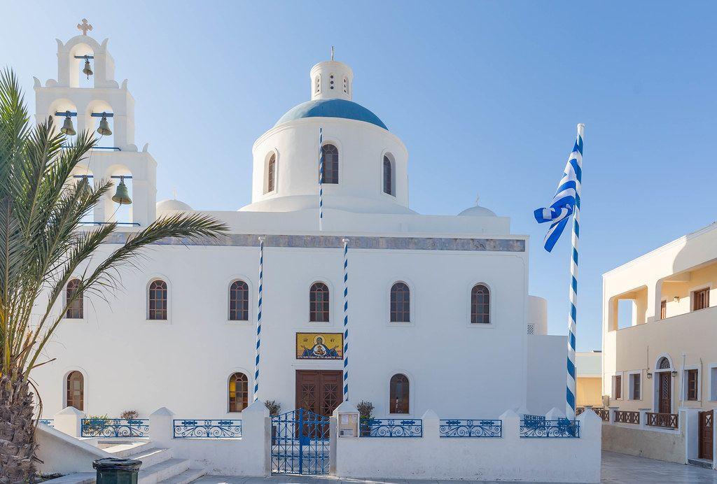 Panagia Platsani Kirche in Oia, Santorin mit blauer Kuppel, Kirchenglocken und griechischer Flagge
