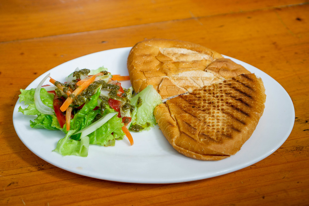 Panini Sandwich with Ham and Cheese and Salad as Side Dish on a White Plate as a Snack at a Restaurant