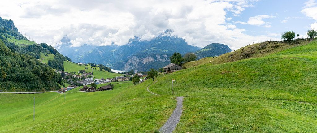 Panorama of Swiss green hills with path, village, mountains and lake Lucerne
