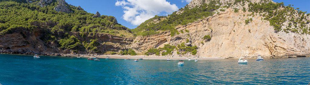 Panoramabild: Boote vor dem Strand Platja des Coll Baix. Bootsausflug an der Nordküste Mallorcas