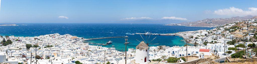 Panoramabild der Hauptstadt Mykonos mit weißen Häusern, einer Windmühle und blauem Meer