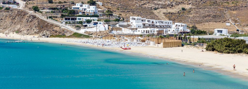 Panoramic image of the sandy beach of Kalo Livadi in Mykonos with the blue waters of the Aegean Sea