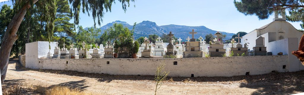Panoramic photo of cemetery and chapel with graves and crosses. Agios Charalampos near Halki, Naxos