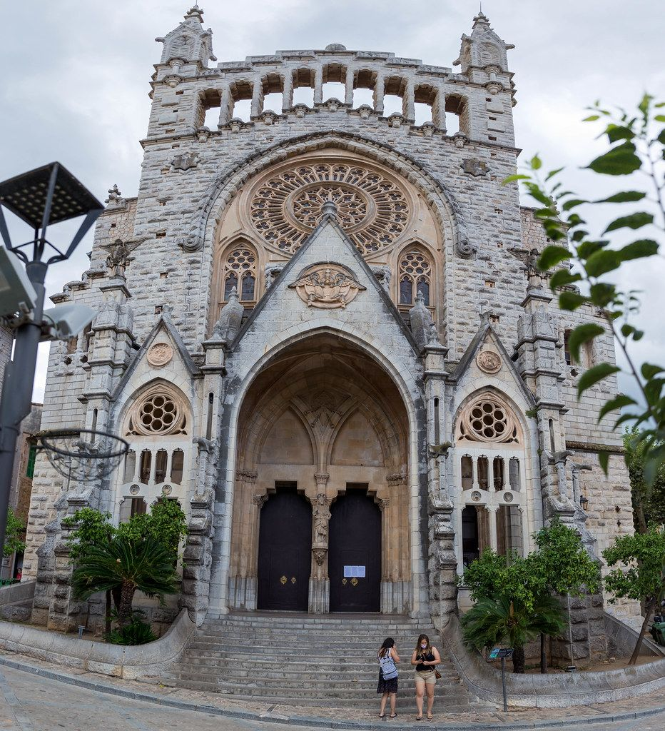 Panoramic photo of the modernist facade of St Bartholomew's church in the main square of Sóller