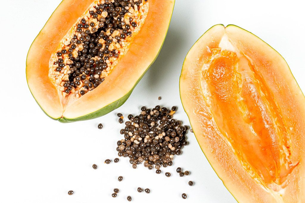 Papaya halves with and without seeds on a white background