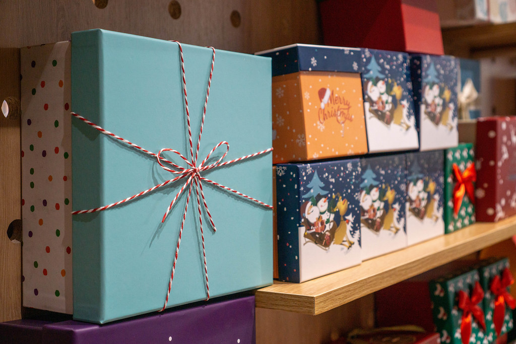 Paper Gift Boxes in different Sizes in Christmas Design on a Wooden Shelf in a Store
