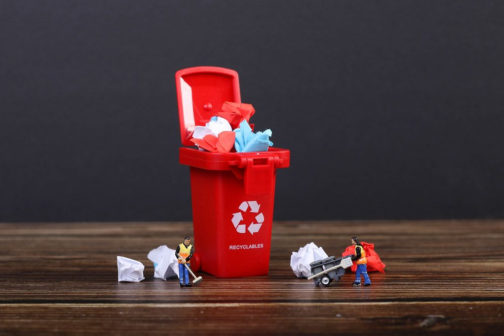 Paper in red recycle bin with tiny cleaning workers