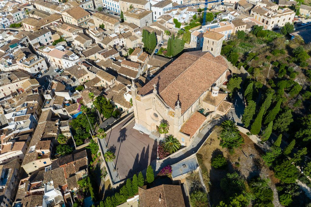 Parish church Transfiguració del Senyor in Artà, Majorca. Aerial view surrounded by houses and trees