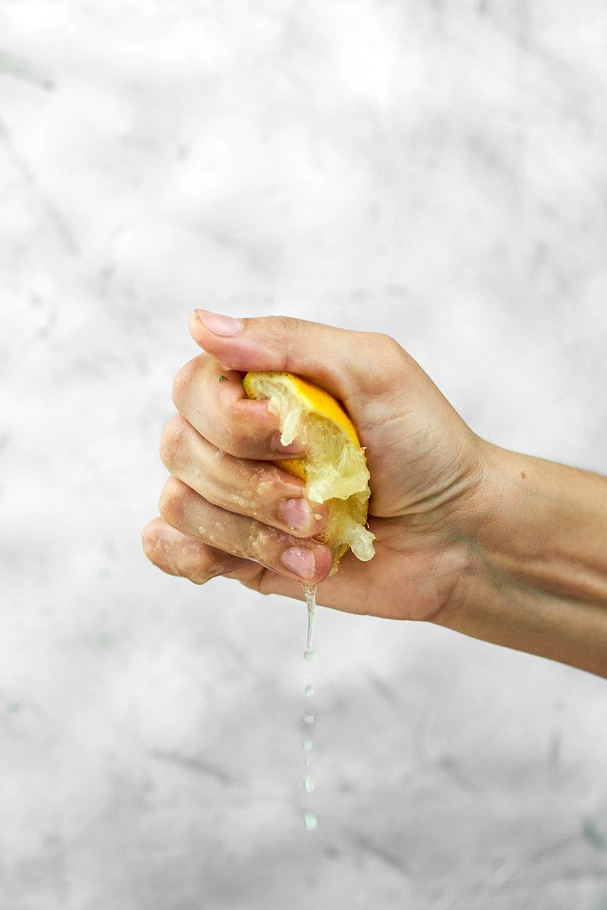 Partial view of woman hand squeezing fresh lemon