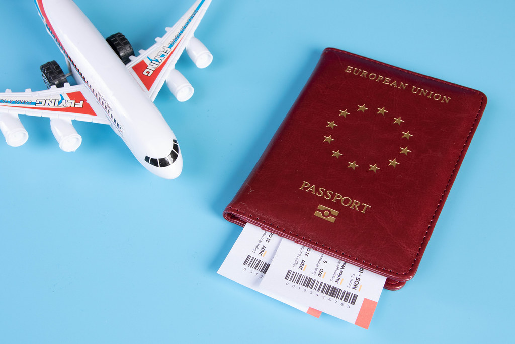 Passport and tickets with small airplane on a blue background