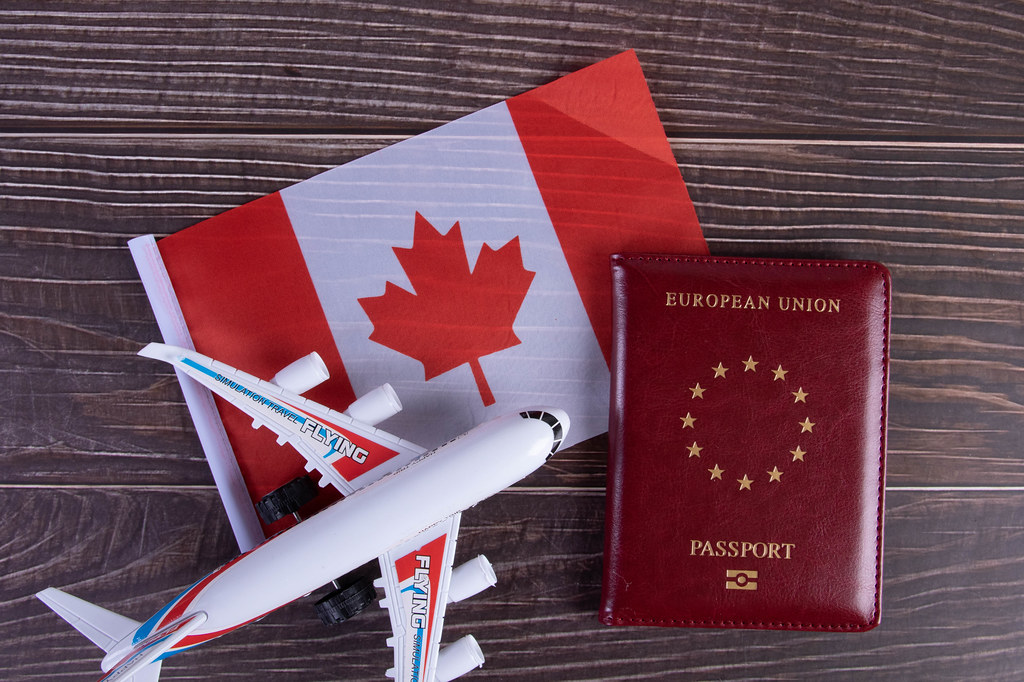 Passport, miniature airplane and flag of Canada on wooden table