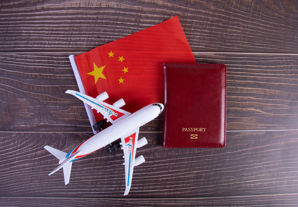 Passport, miniature airplane and flag of China on wooden table