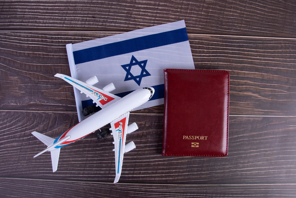 Passport, miniature airplane and flag of Israel on wooden table