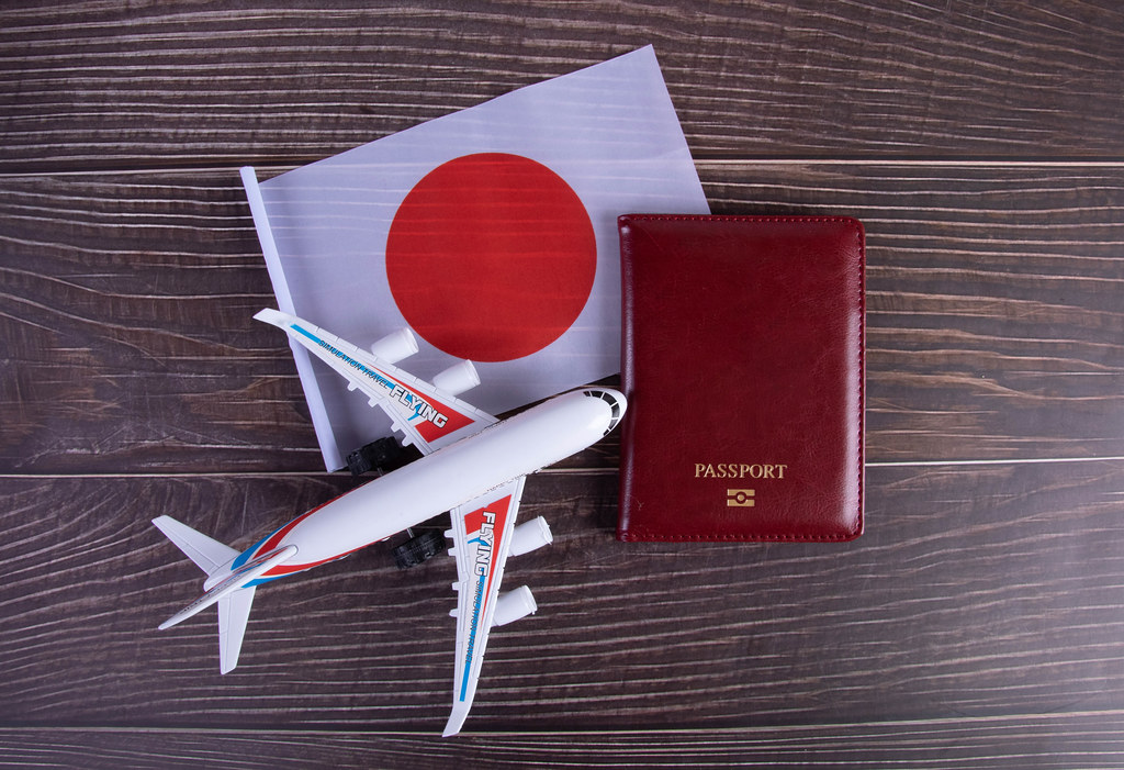 Passport, miniature airplane and flag of Japan on wooden table