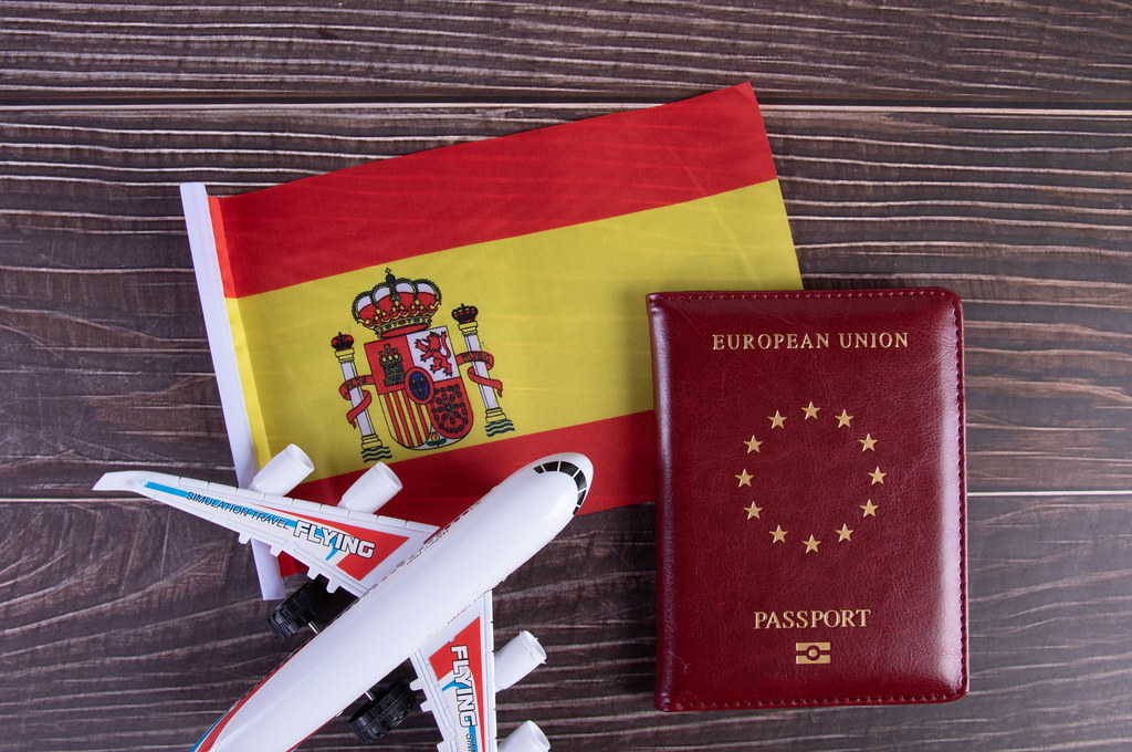 Passport, miniature airplane and flag of Spain on wooden table