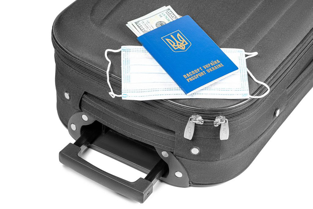 Passport with dollars, medical mask and suitcase