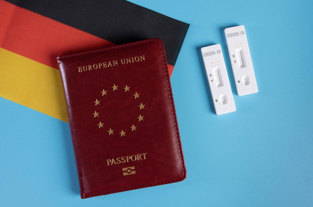 Passport with flag of Germnay and rapid antigen tests