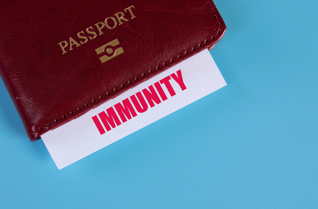 Passport with Immunity card on blue background