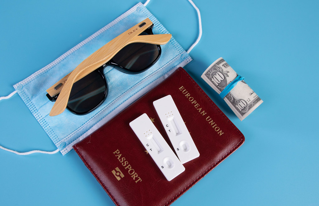 Passport with Rapid antigen test, face mask and sunglasses on blue background
