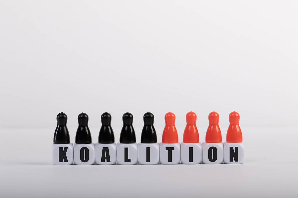 Pawn figurines with cubes and Koalition text on white background