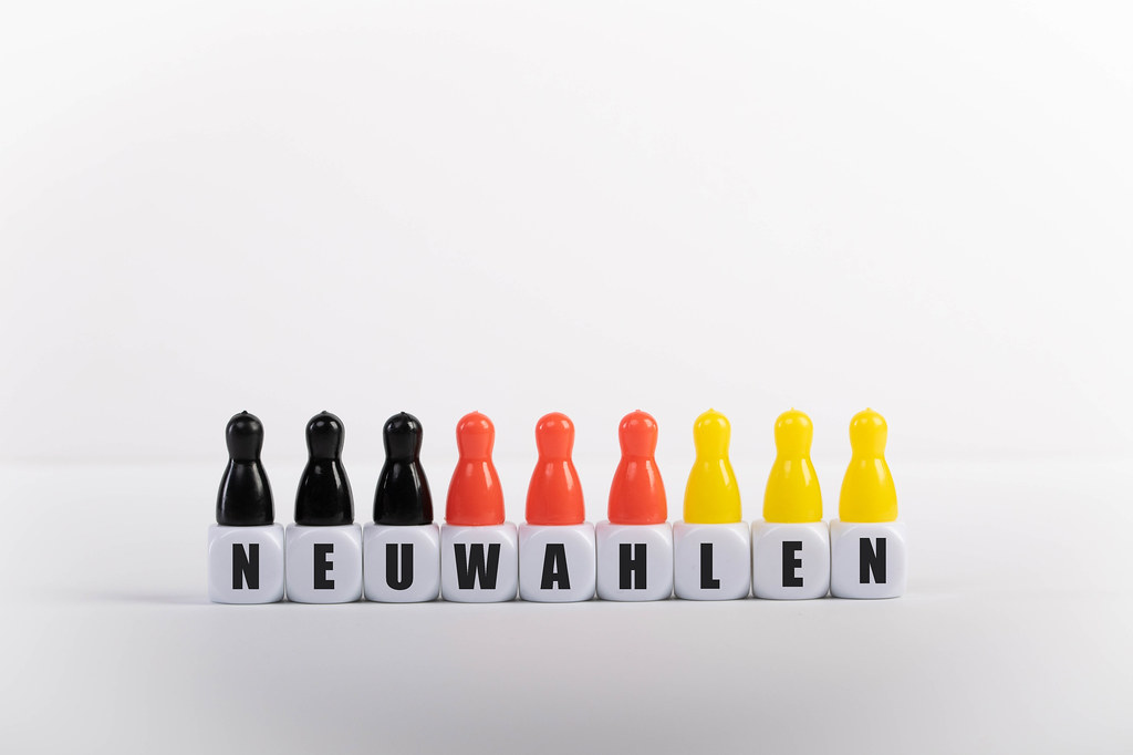 Pawn figurines with cubes and Neuwahlen text on white background