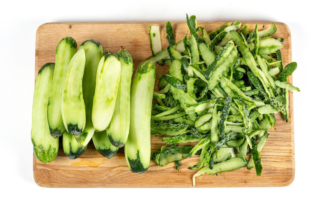 Peeled cucumbers and their green peel on wooden kitchen board