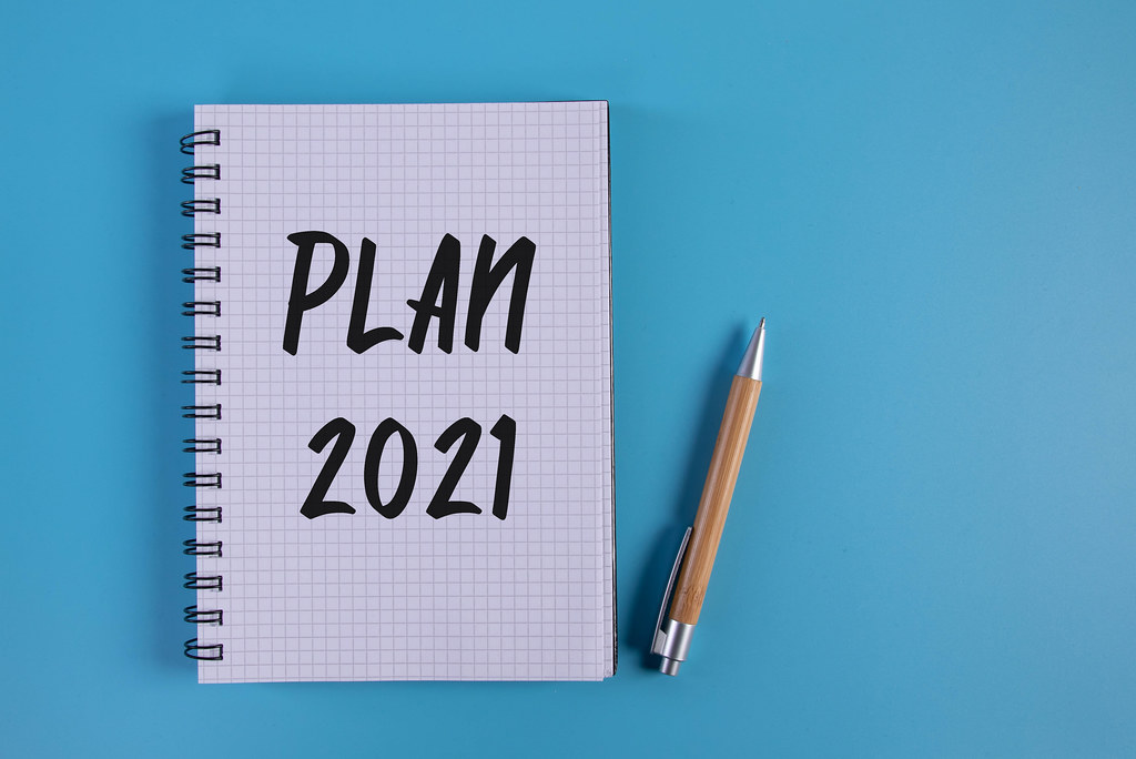 Pen and notebook with Plan 2021 text on blue background