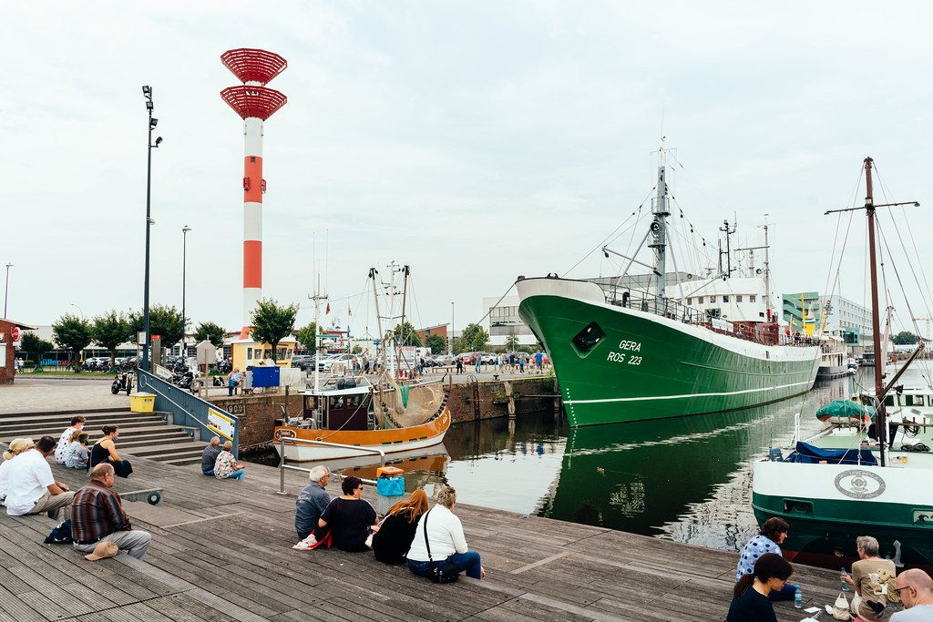 People seating on the embarkment at the Bremerhaven port with big and small ships parked