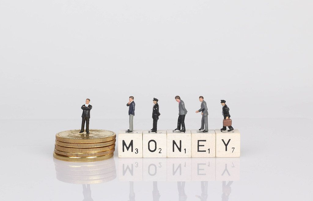 People standing on wooden cubes with money text