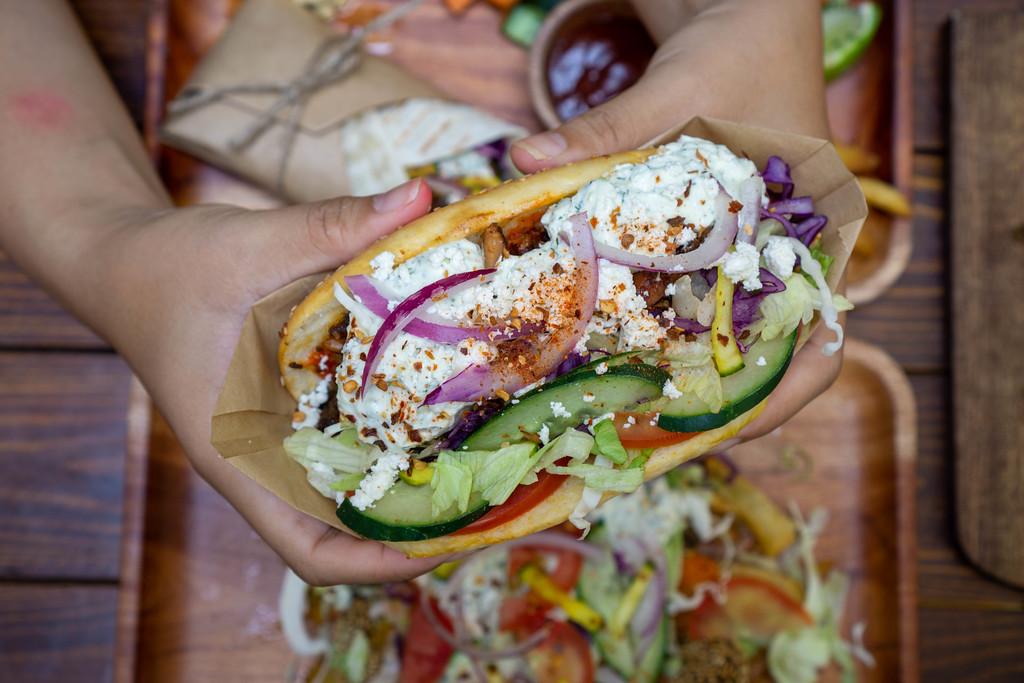 Person hält einen Döner Kebab mit Hähnchenfleisch, frischem Gemüse, Zwiebeln und Tzatziki Soße in beiden Händen von oben fotografiert