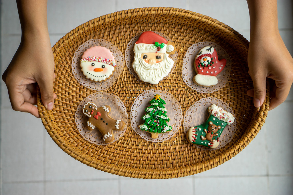 Person holding Oval Rattan Tray with Christmas Gingerbread Cookies in different Forms with both Hands