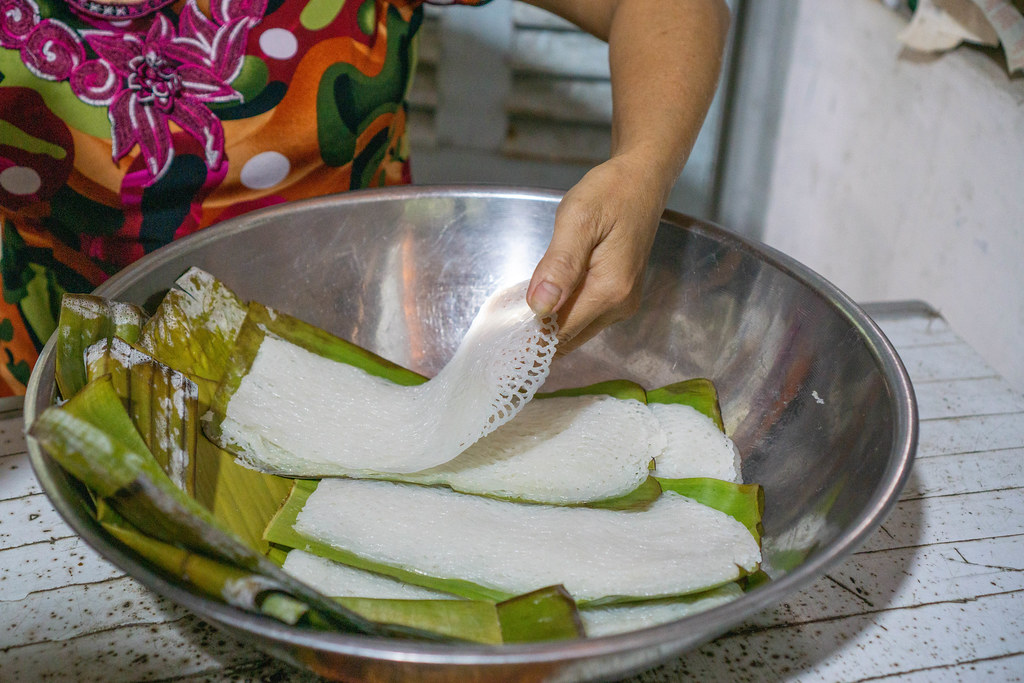 Person placing Vietnamese Rice Vermicelli Banh Hoi on Banana Leaves in a Bowl at a Noodle Factory in the Mekong Delta in Vietnam