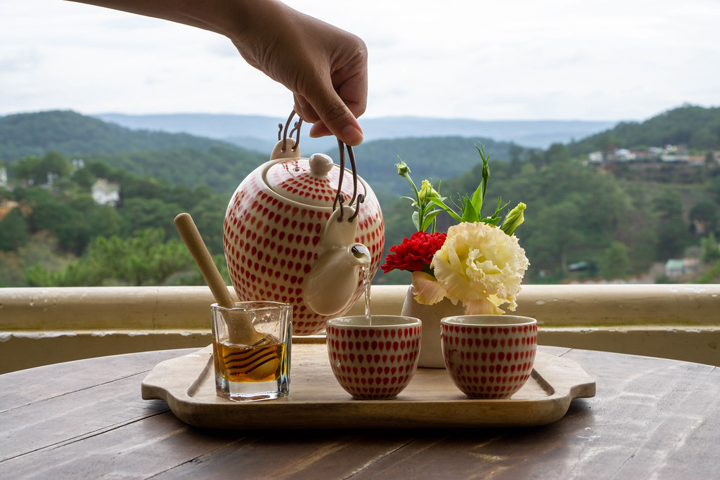 Person pouring Hot Green Tea from a Tea Pot into two Small Ceramic Cups on a Wooden Tray with Honey and Flowers with Mountain View in the Background