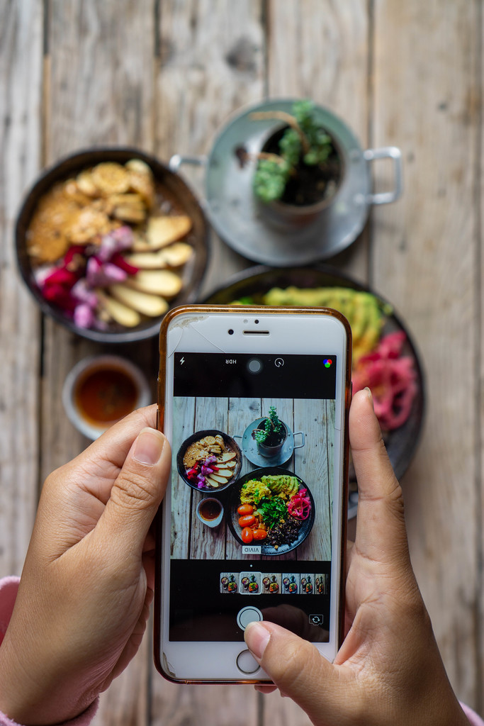 Person taking a Food Photo with an iPhone for Instagram of a Healthy Vegan Breakfast on a Wooden Table