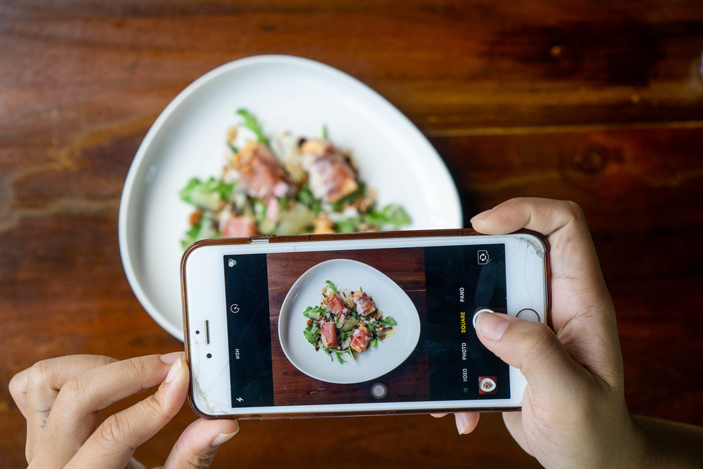 Person taking Food Photo with a Smartphone of Honeydew Melon wrapped in Parma Ham with Arugula, Parmesan Ham and Balsamic Dressing on a Ceramic Plate