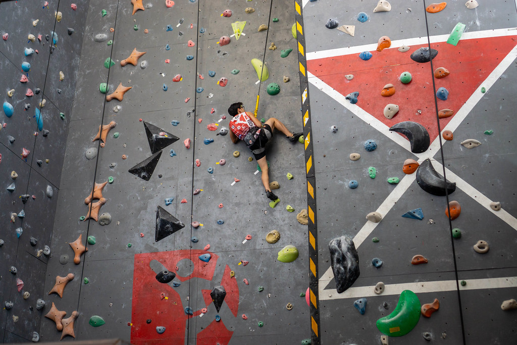 Person with Safety Harness and Climbing Shoes is attached to a Rope and Climbing up a Wall in an Indoor Climbing Hall