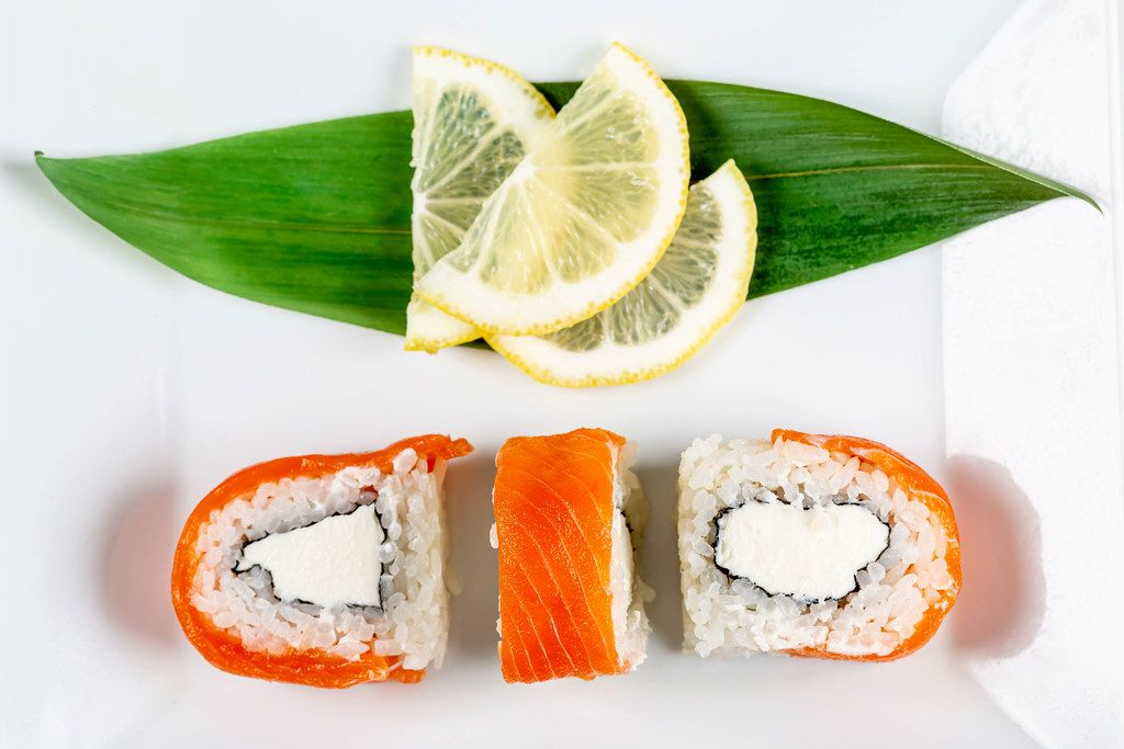 Philadelphia sushi on a white plate with lemon slices, top view