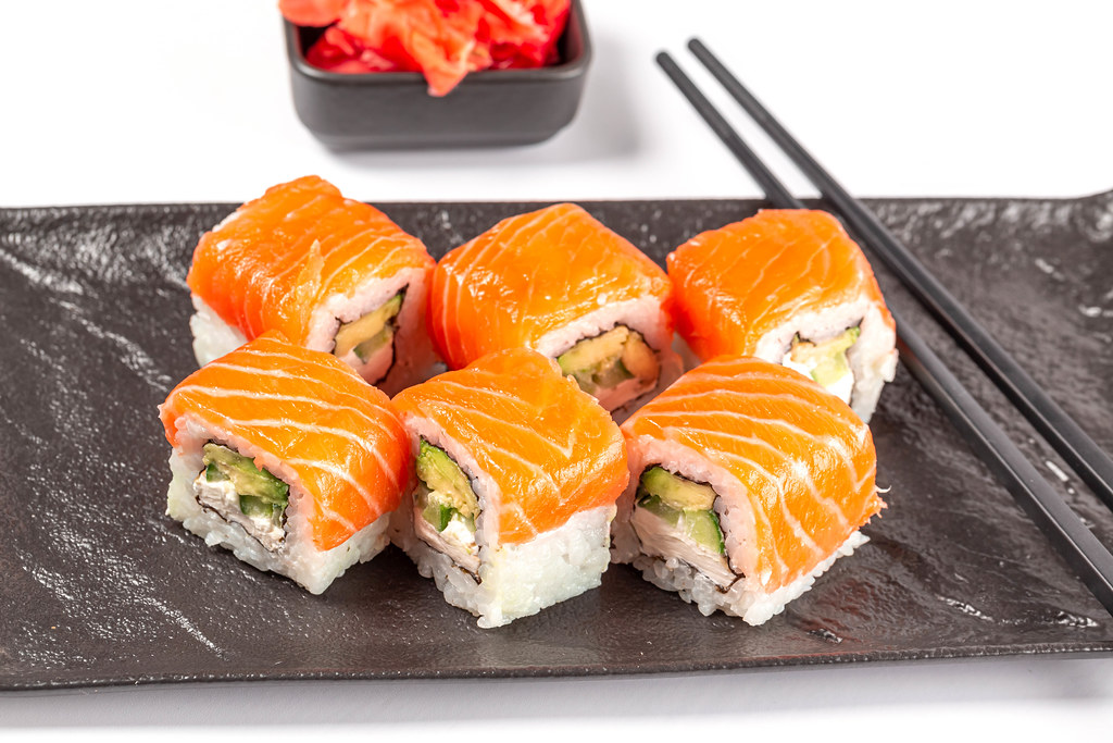 Philadelphia sushi with salmon on a black tray with chopsticks