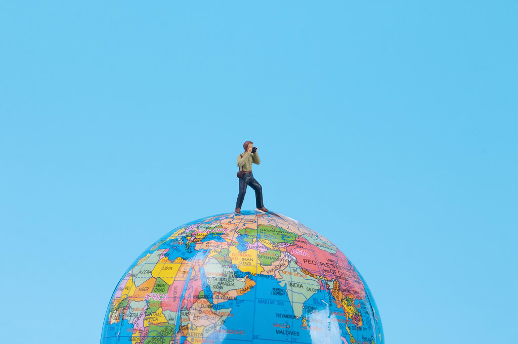 Photographer standing at top of the globe