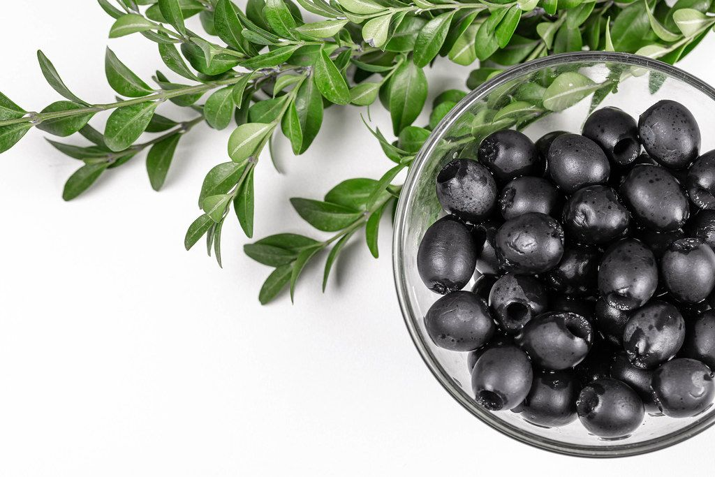 Pickle black olives in a glass bowl and branches withgreen leaves
