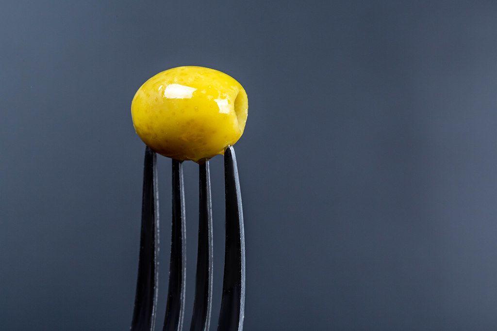 Pickled green olive on a fork on a dark background