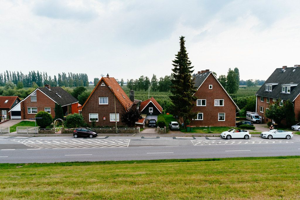 Picture of a typical German countryside with buildings facing the road and fields in the background