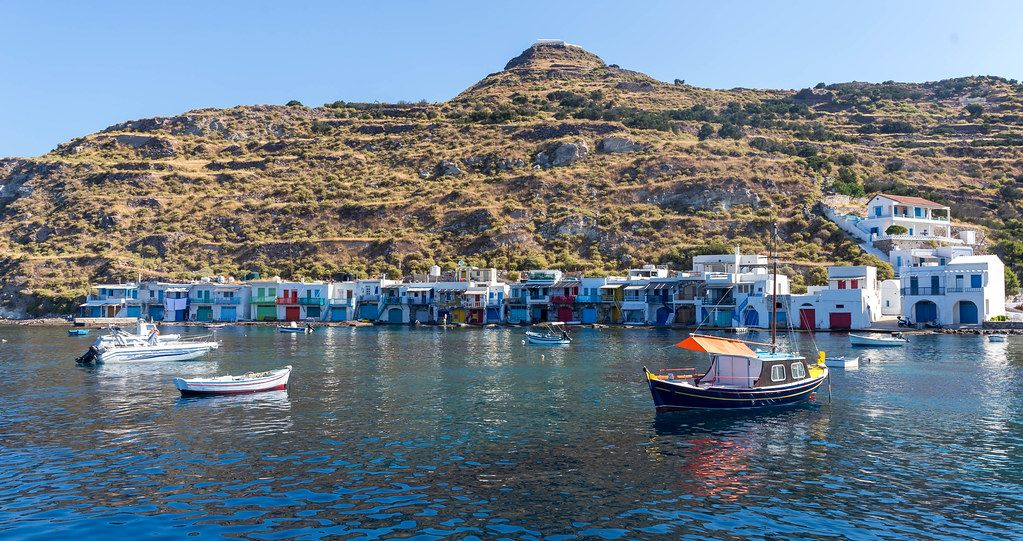 Picturesque Greek scenery on the island of Milos: boats and boathouses sheltered by the cliff in Klima