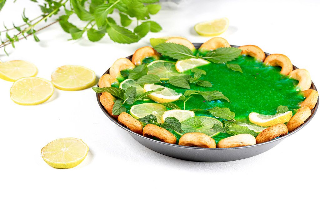 Pie with green mirror glaze, fresh mint leaves and citrus