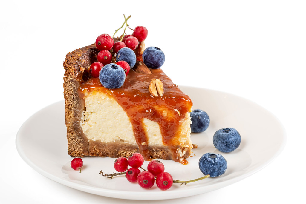 Piece homemade cheesecake with red currant and blueberry