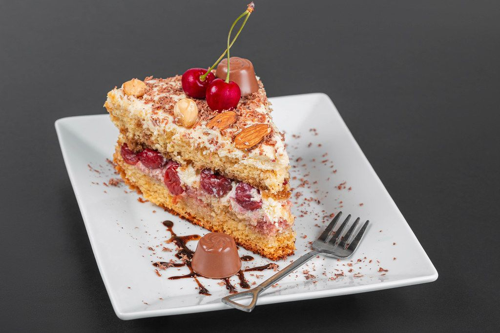 Piece of cake with cherries, chocolate and nuts on a plate with a fork