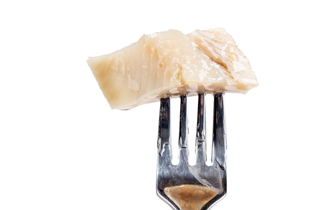 Piece of salted herring fillet on a fork