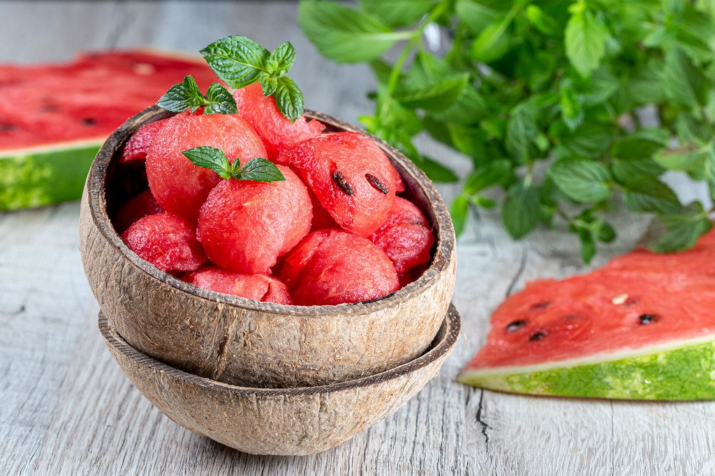 Pieces-balls of fresh red watermelon in a wooden bowl with mint leaves